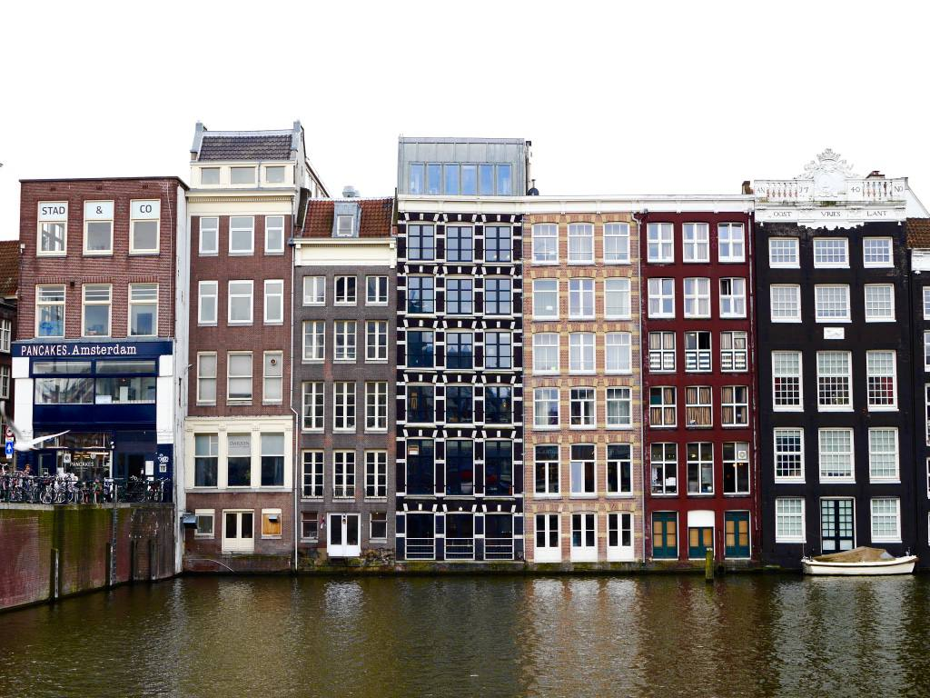 Brown tone canal houses in Amsterdam located on Damrak, one of Amsterdam's most famous streets